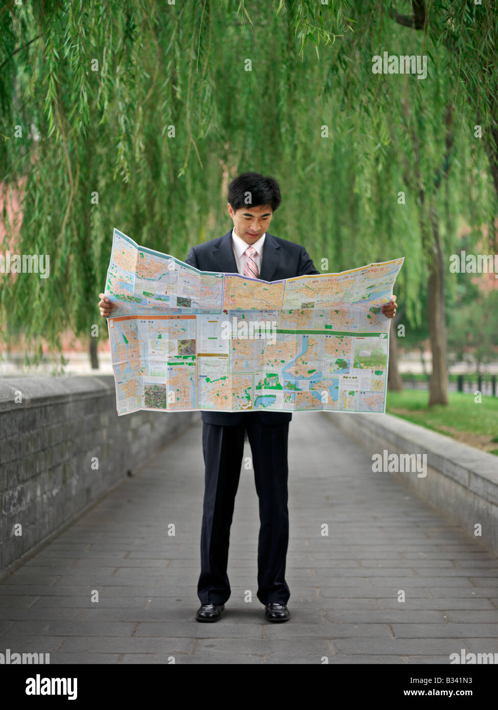 Chinese man looking at a map to help reorient or locate himself. Stock Photo