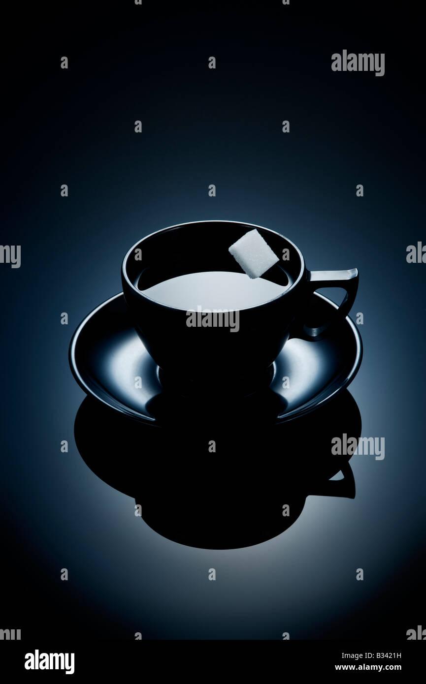 Sugar cube falling into black coffee - Stock Image