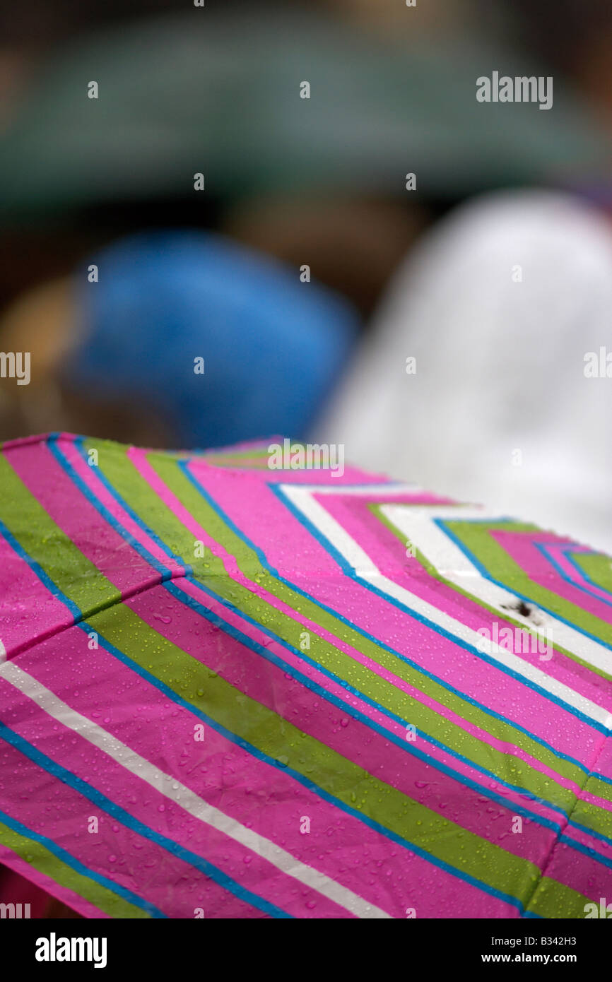multicoloured umbrella being held up in a crowd during rain shower in belfast northern ireland - Stock Image