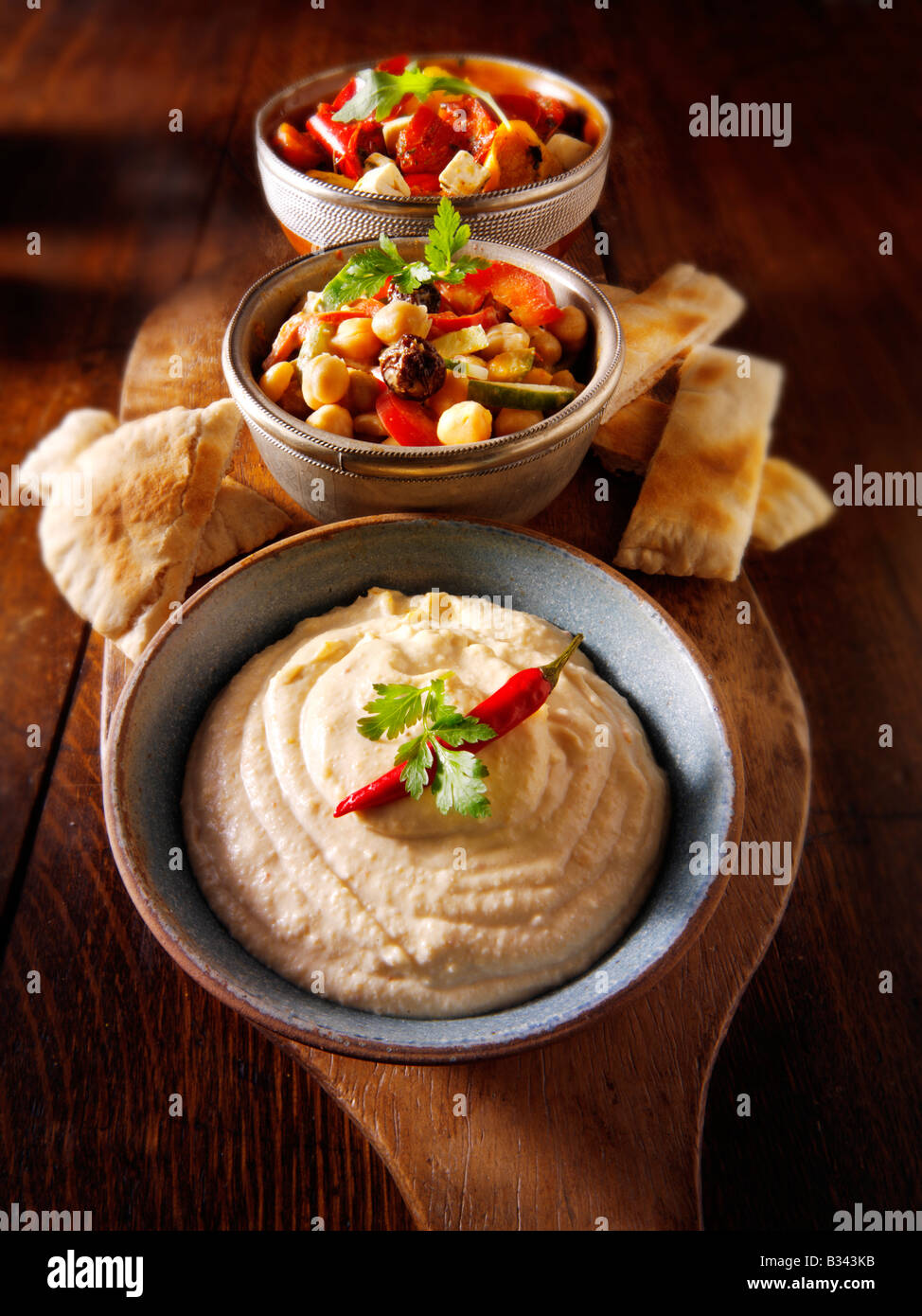 Party Food - From Front - Houmous, [chick pea] salad, marinated Mediterranean roast peppers Stock Photo