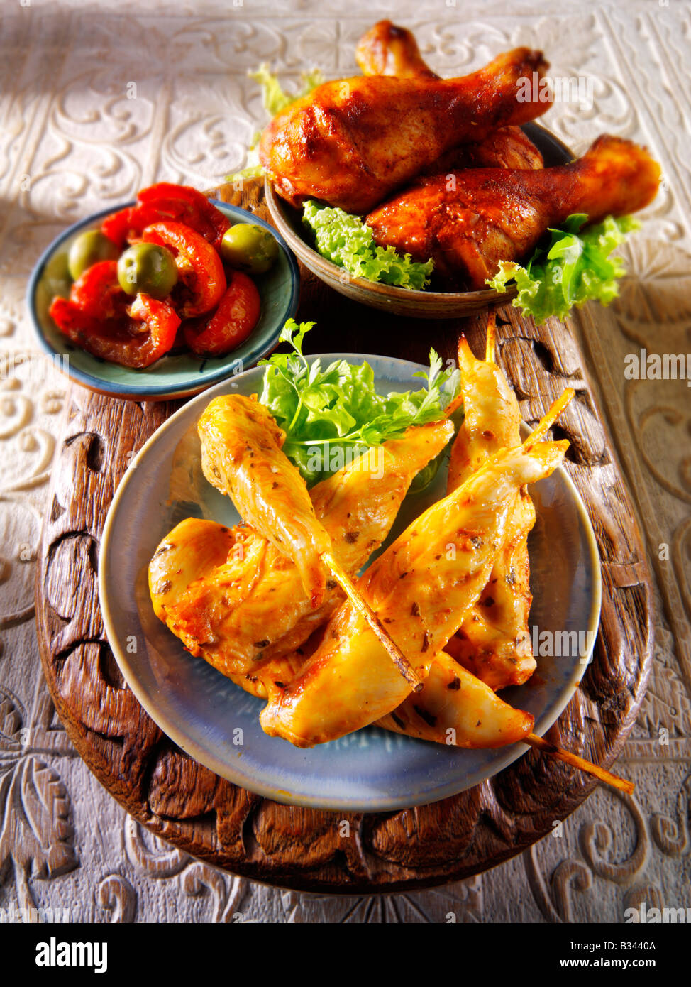 party food - From Front - Marinated chicken skewers, Marinaded chicken drum sticks and sun blushed tomatoes. Stock Photo