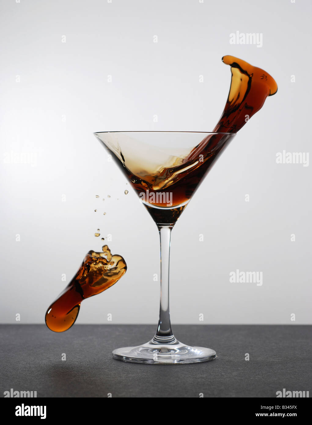 High speed splash of Coke Cola drink in a cocktail glass - Stock Image