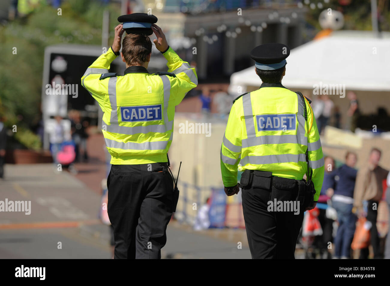A young Police cadet lifts his hat for some relief while on patrol at a public event in Eastbourne in the sunshine. - Stock Image