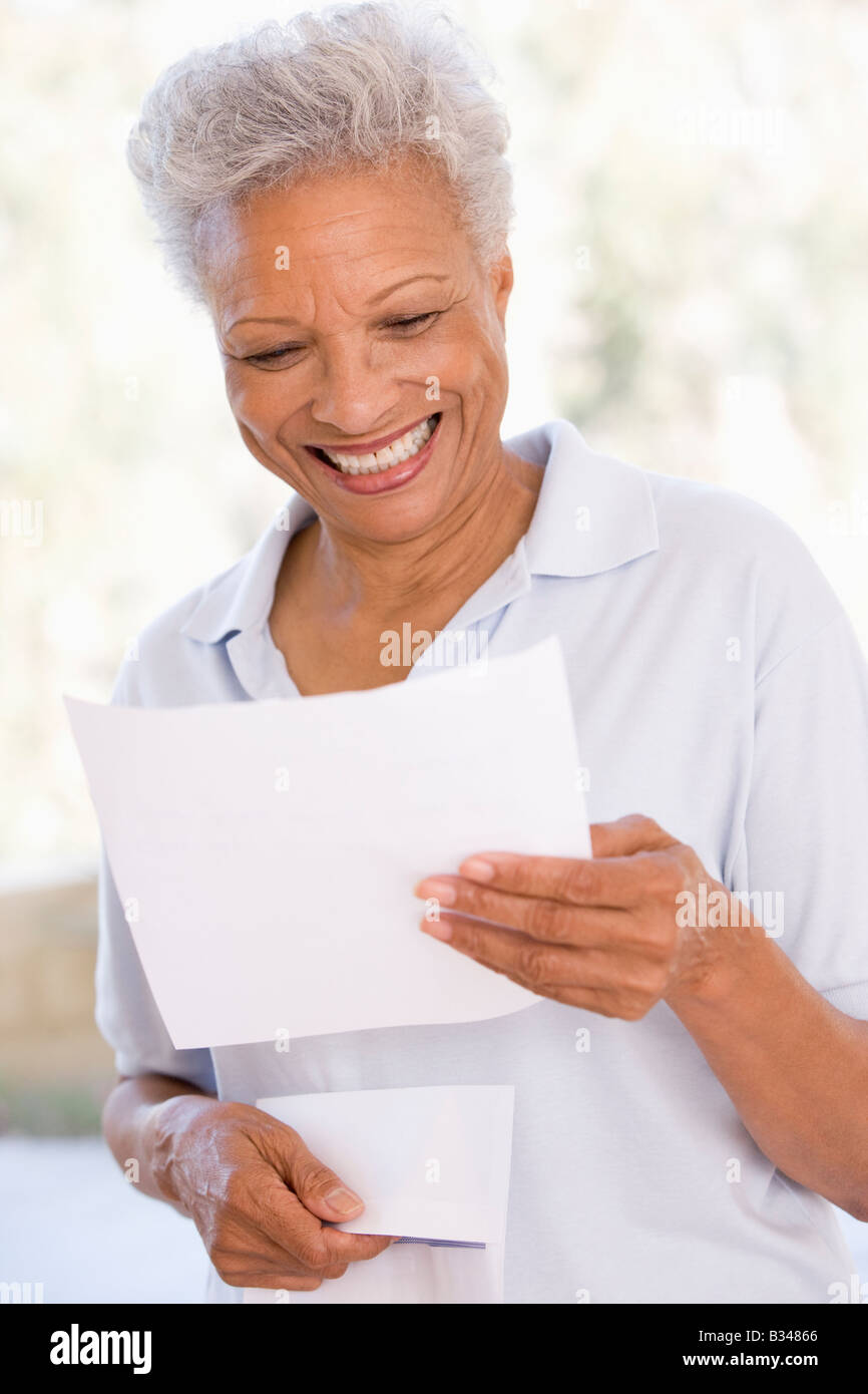 Woman reading letter smiling - Stock Image