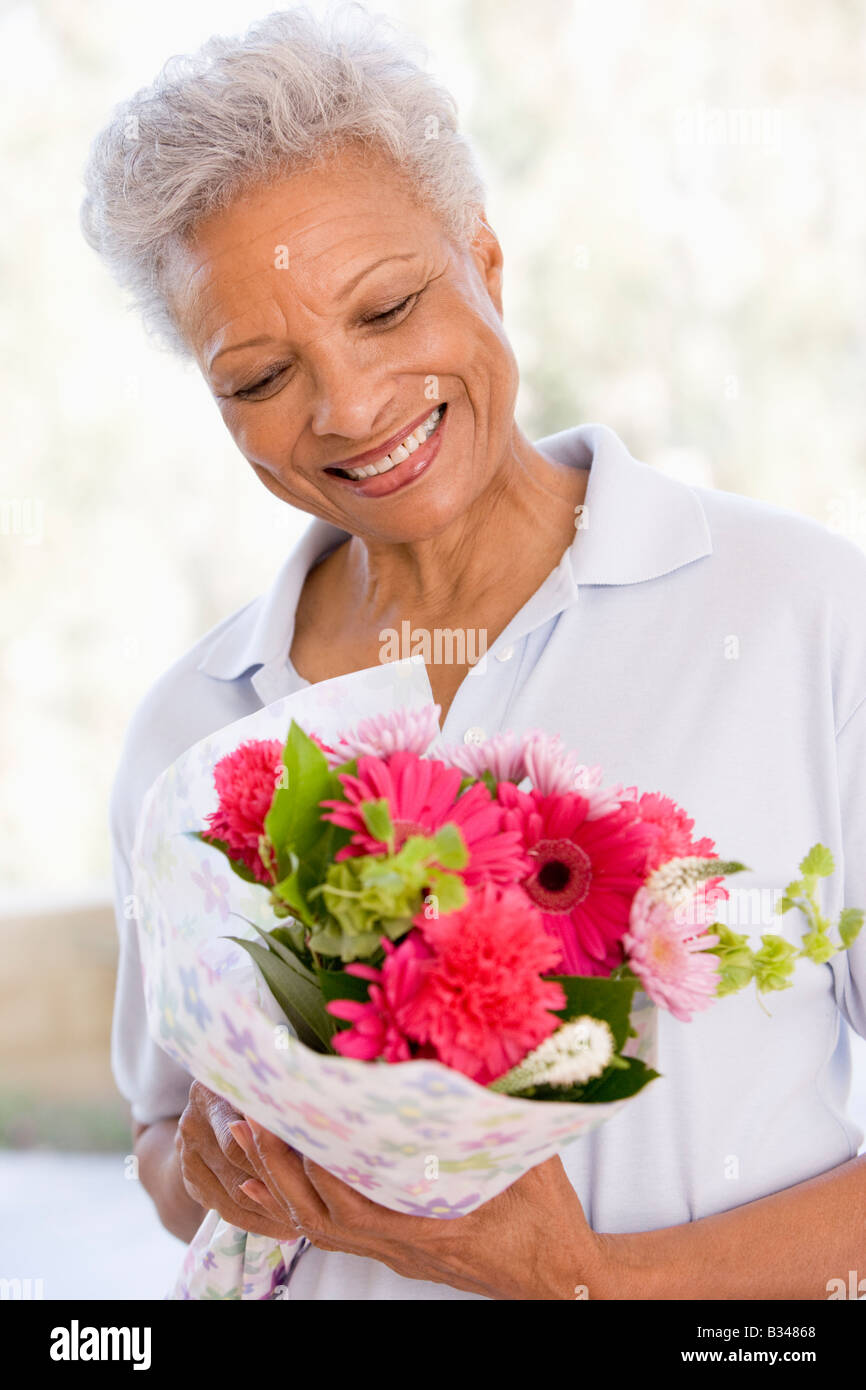 Woman holding flowers and smiling - Stock Image