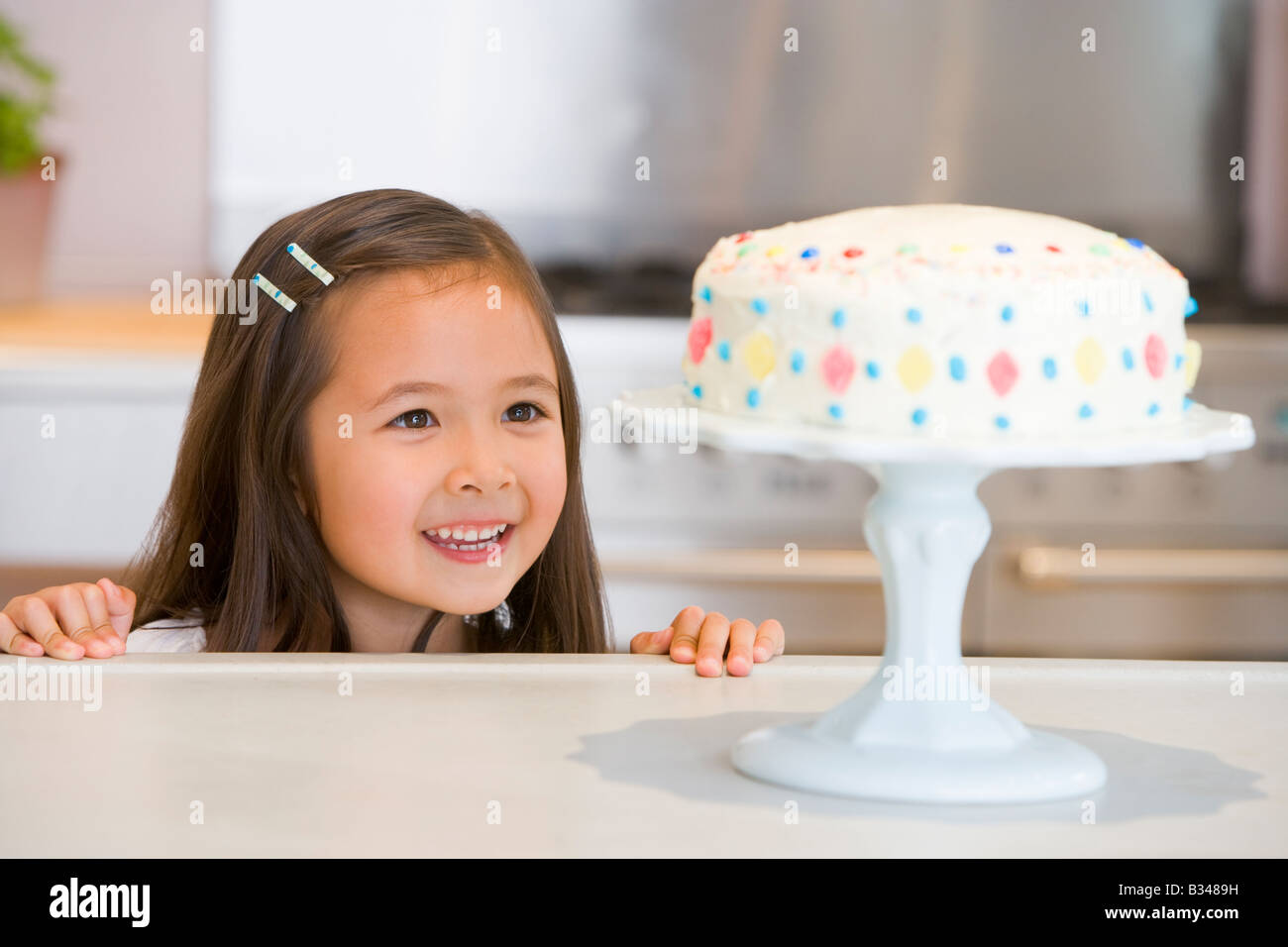 Young girl at kitchen counter looking at cake smiling - Stock Image
