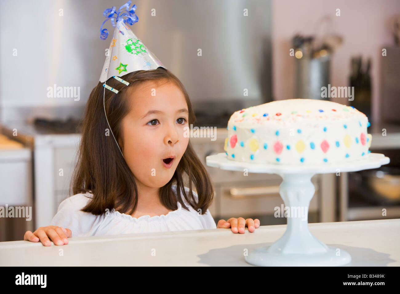 Young girl wearing party hat at kitchen counter looking at cake smiling - Stock Image