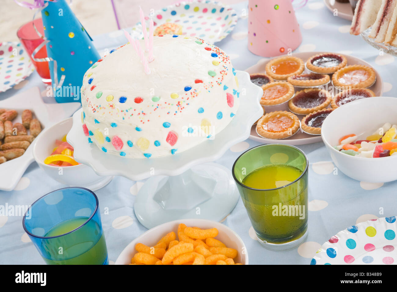 Birthday party table setting with food - Stock Image