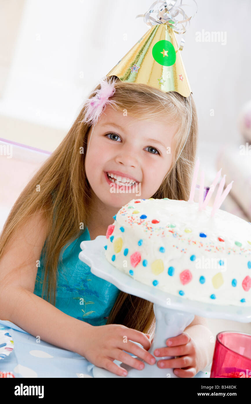 Young girl wearing party hat with birthday cake smiling Stock Photo