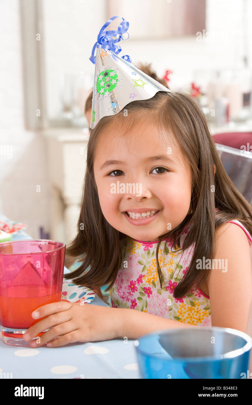 Young girl wearing party hat at table smiling - Stock Image