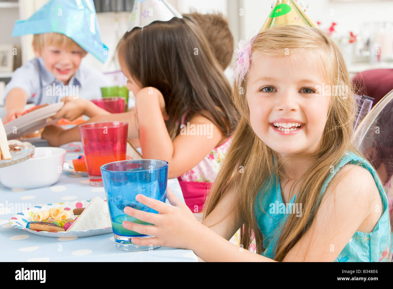 Young girl at party sitting at table with food smiling - Stock Image