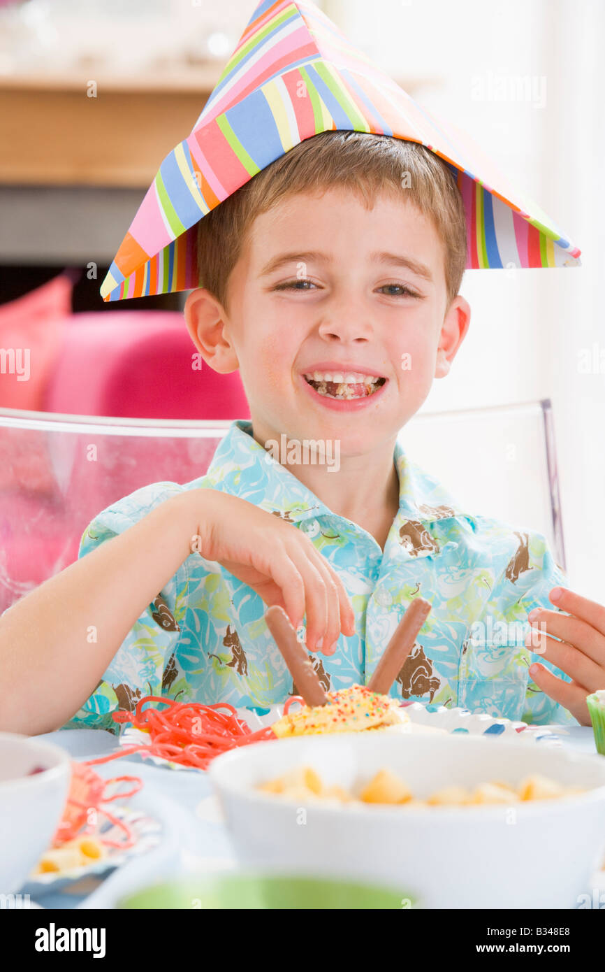 Young boy at party sitting at table with food smiling - Stock Image