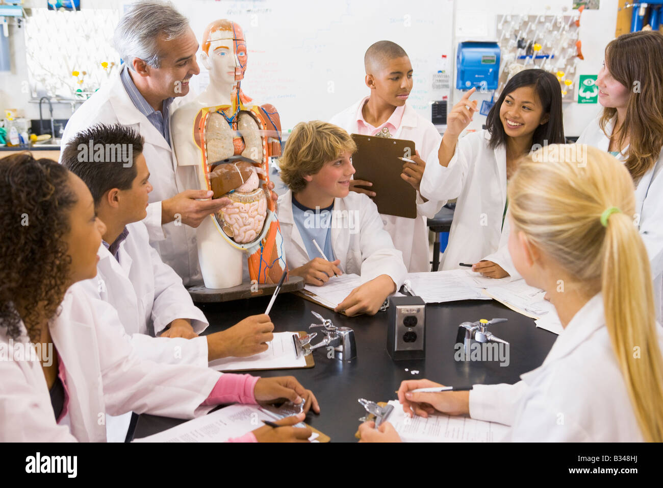 Students in biology class with teacher - Stock Image
