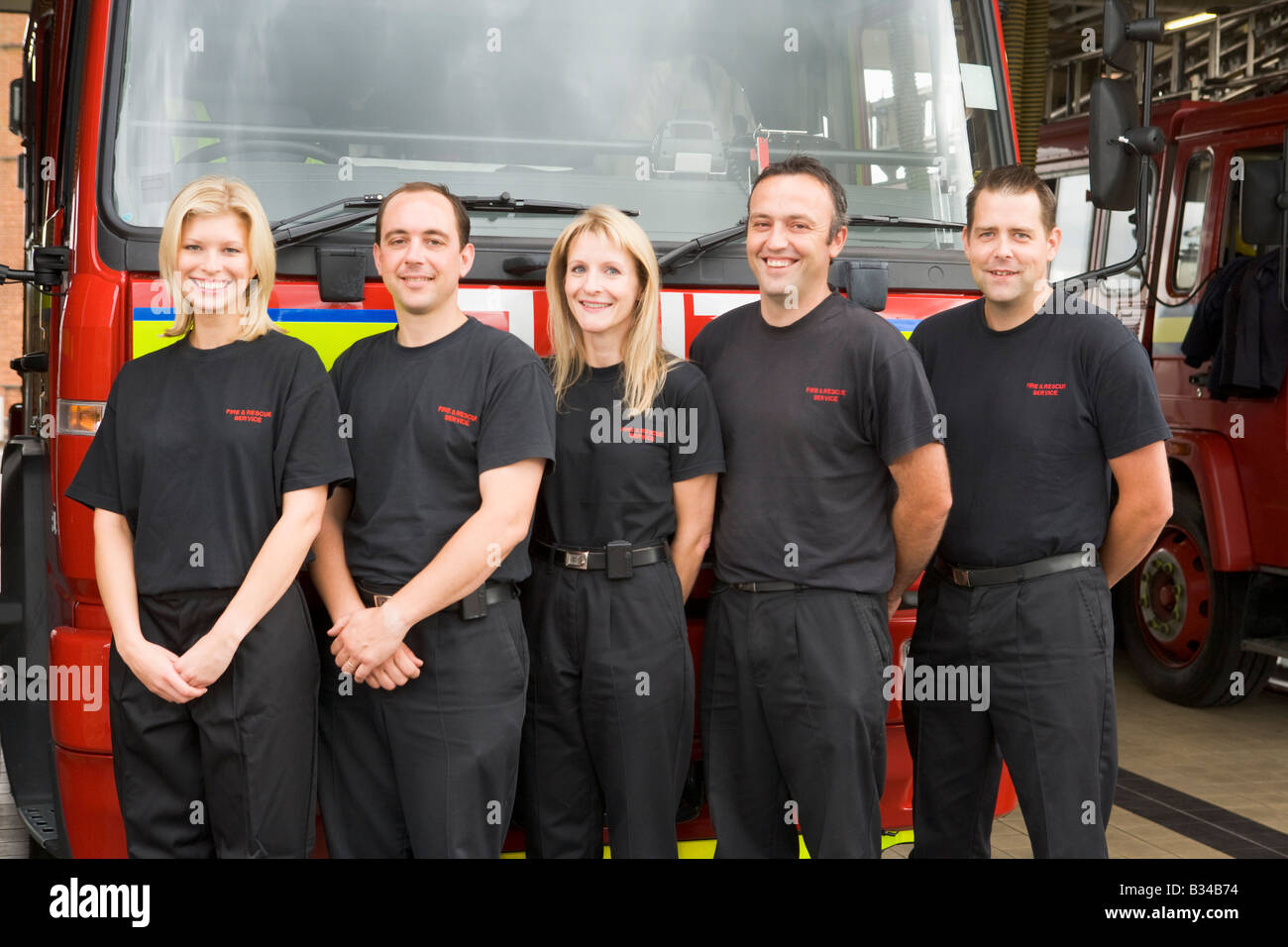 Five firefighters standing in front of fire engine - Stock Image