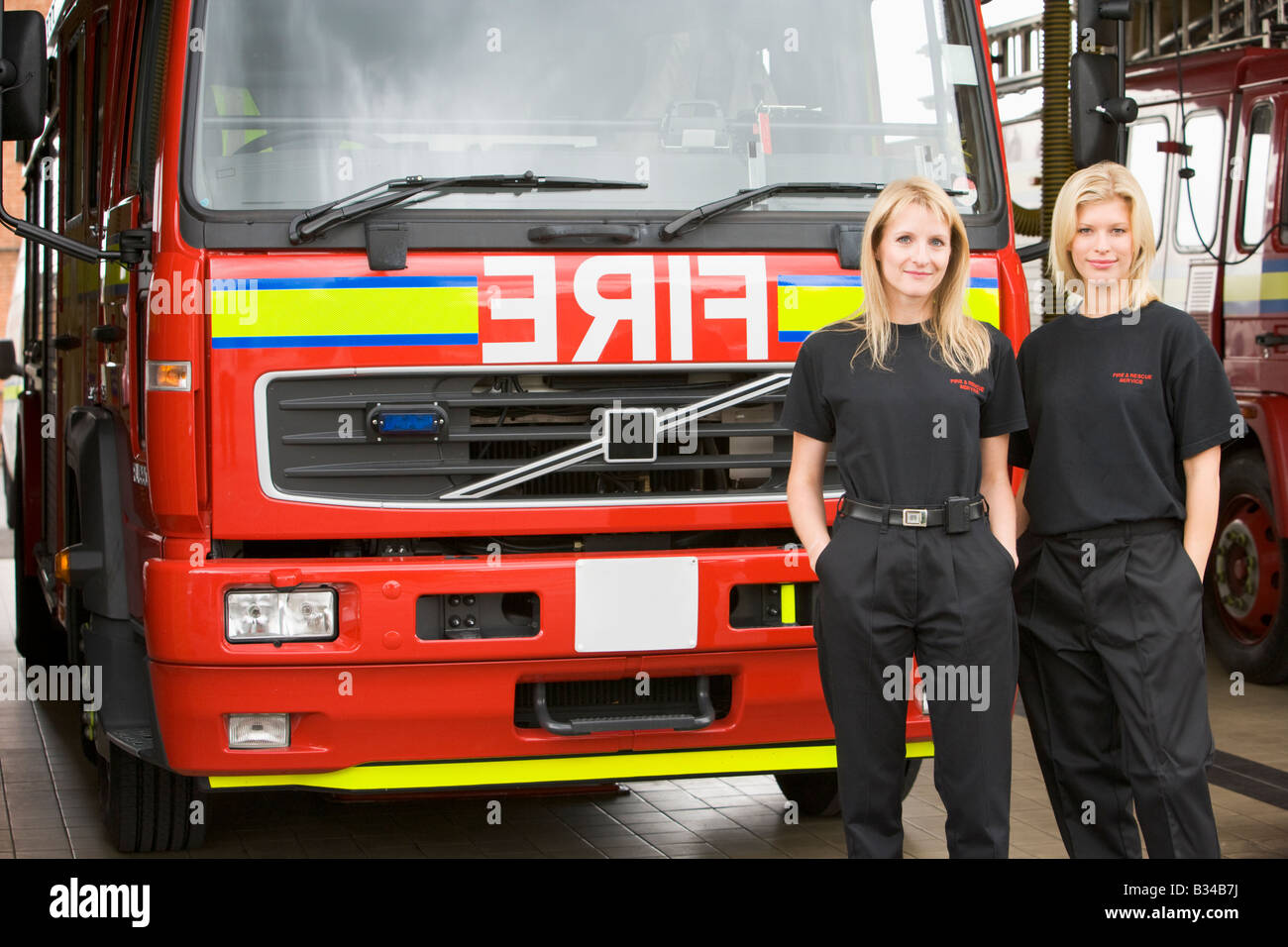 Two firefighters standing in front of fire engine - Stock Image