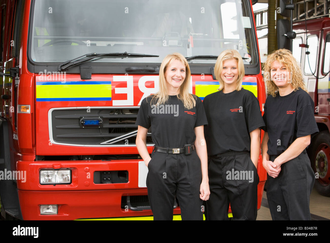 Three firefighters standing in front of fire engine - Stock Image