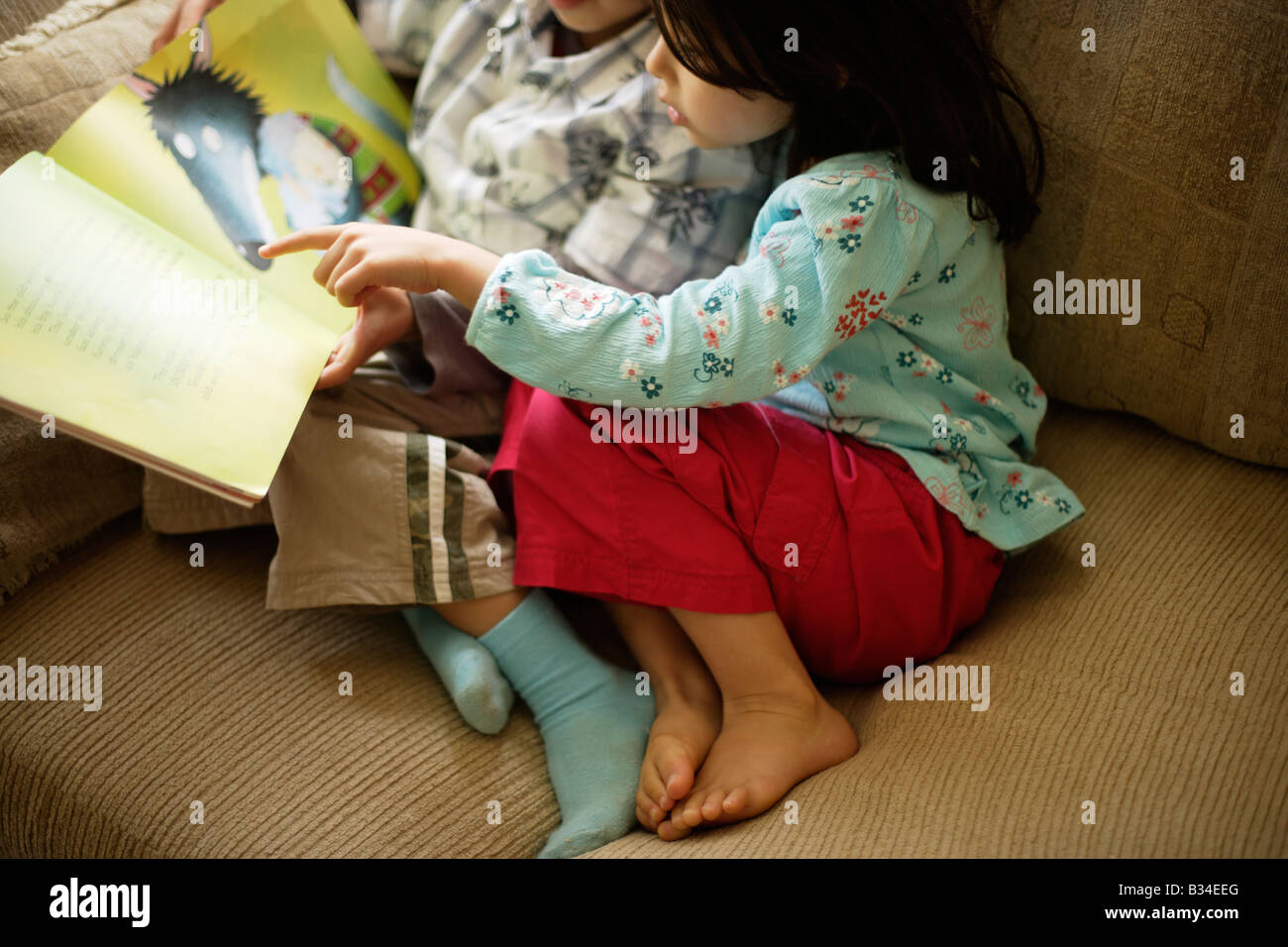 Boy aged six reads a story to his little sister aged five - Stock Image