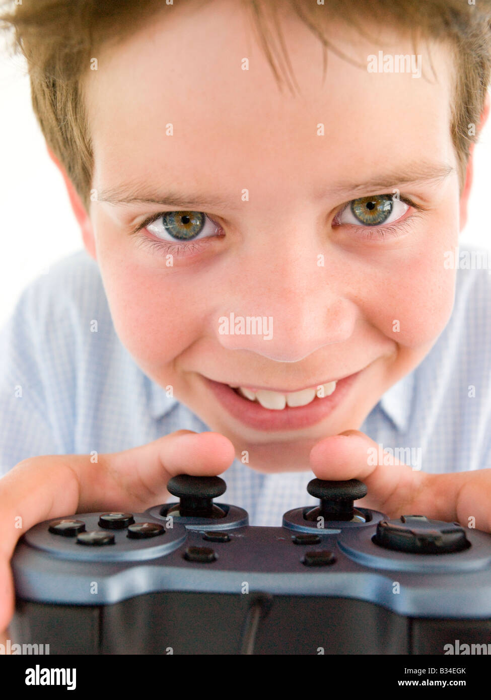 Young boy using videogame controller smiling - Stock Image