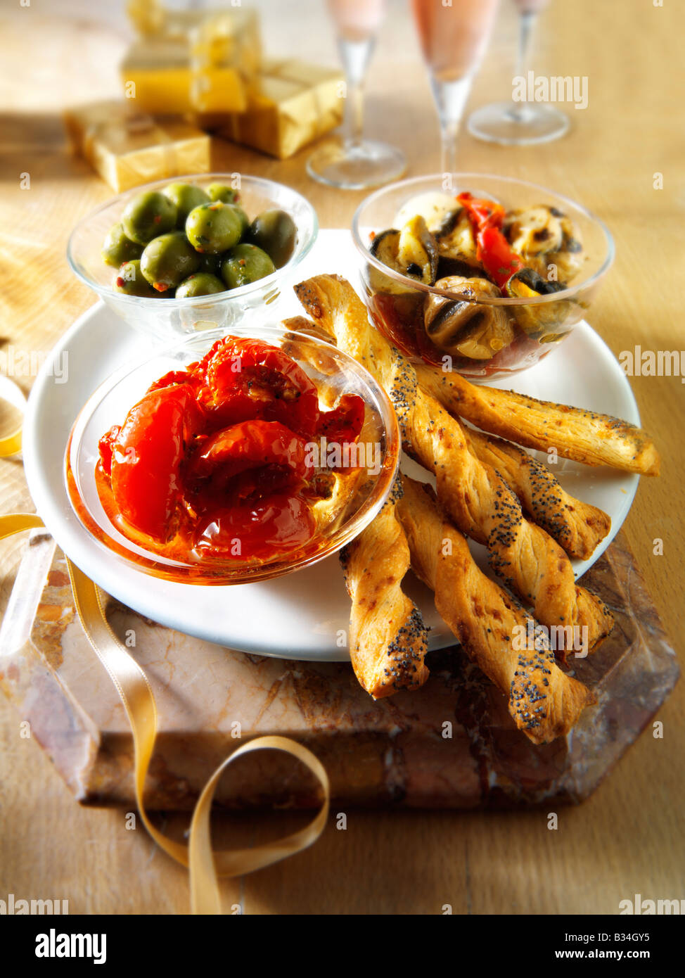 Party Food anti pasta - sun blushed tomatoes, mushroom and roast vegetables and olives with bread sticks. - Stock Image