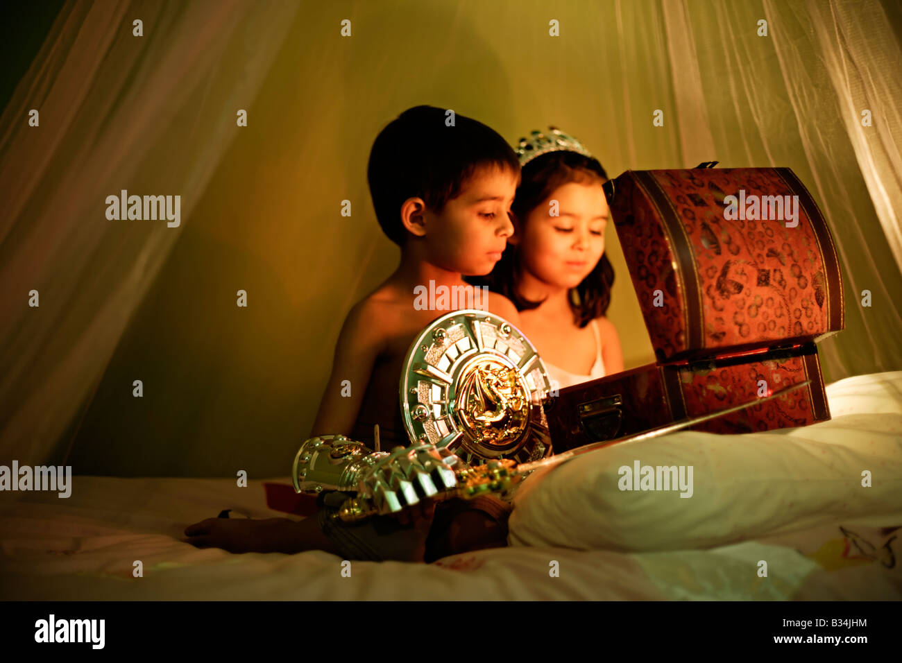 The magical treasure chest Five year old girl and six year old boy at play Brother and sister mixed race - Stock Image