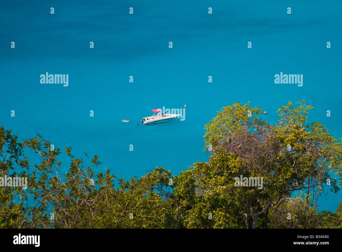 Boat anchored in the Caribbean Sea off the caribbean island of St John in the US Virgin Islands - Stock Image
