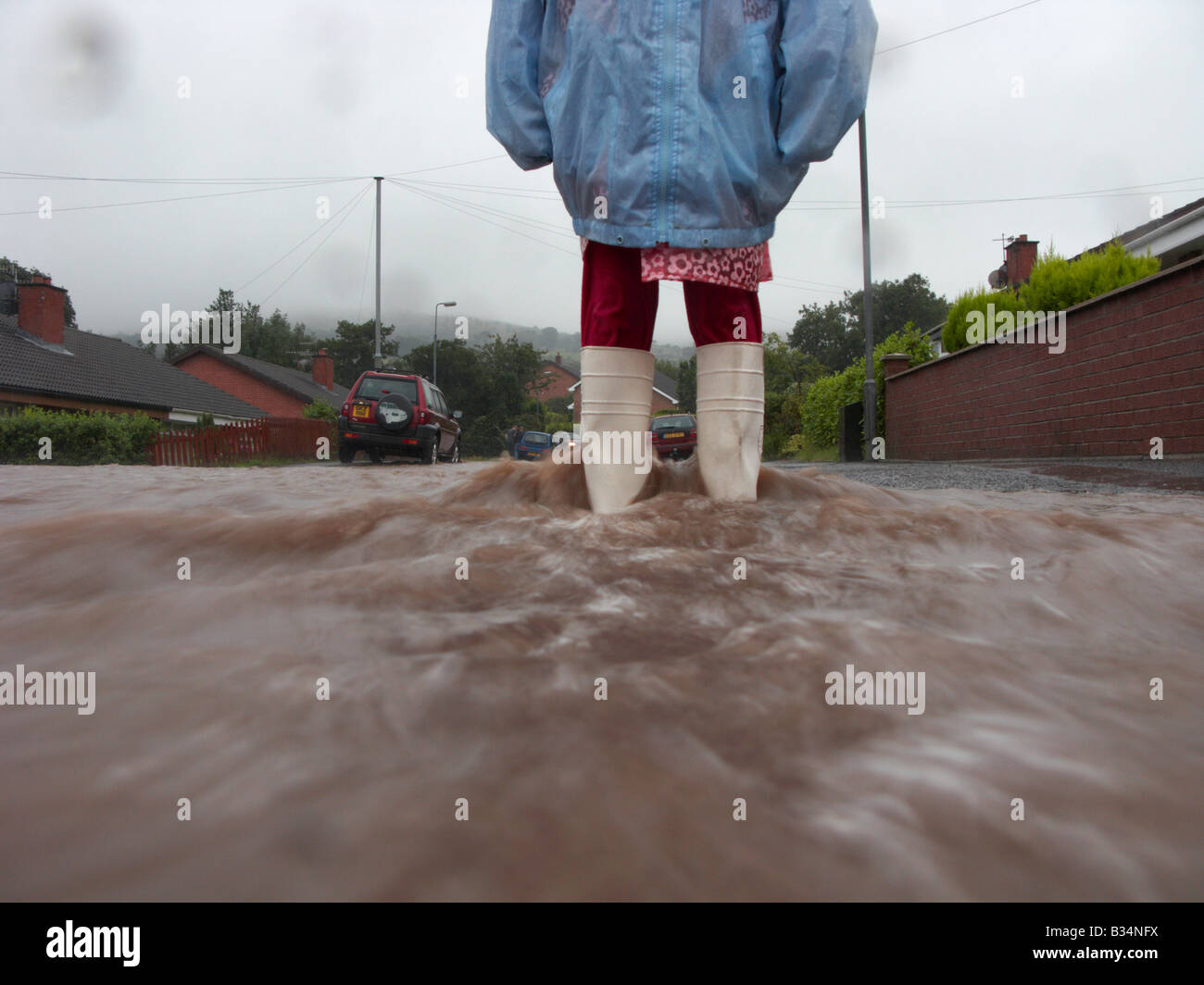 young girl wearing raincoat and wellington boots standing in water from rain and river overflow flooding a street - Stock Image