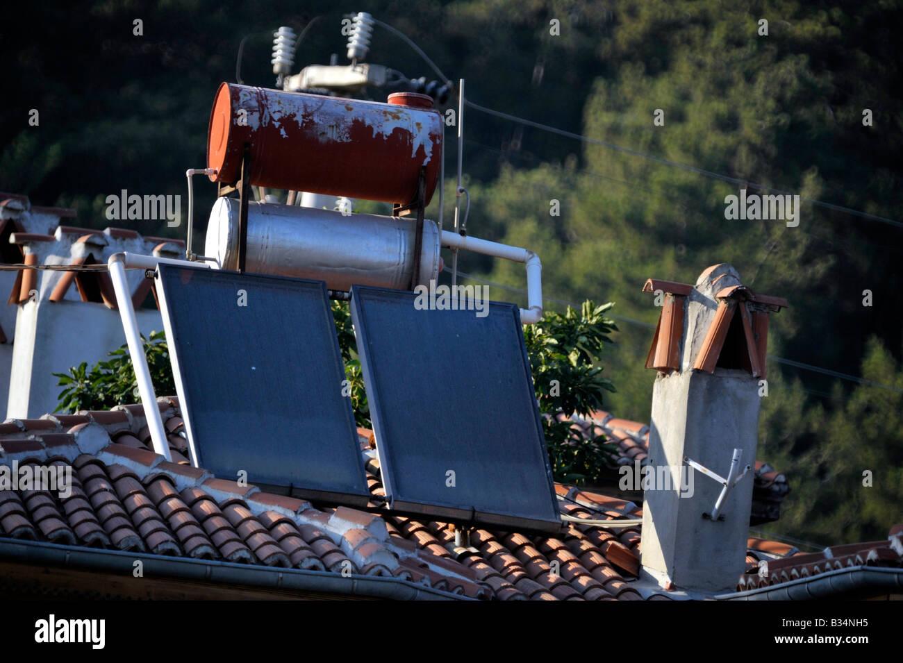 solar heating panels and water storage tank on Turkish house roof Akyaka Turkey - Stock Image