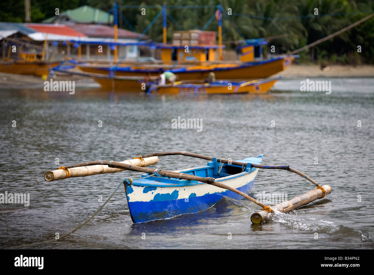 a small weathered bangka boat tied to the beach in mansalay