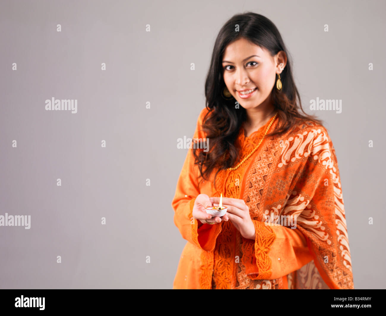A malay lady holding oil lamp - Stock Image