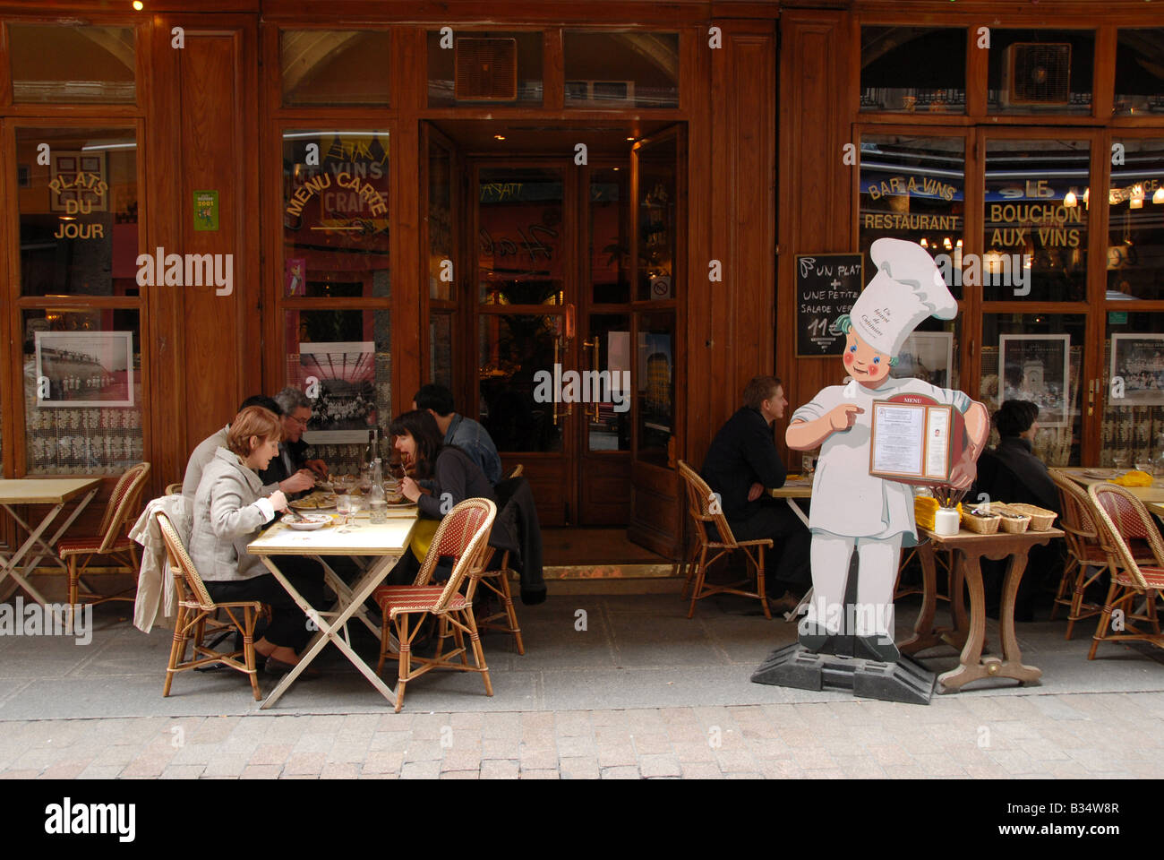 Customers enjoying a lunch outside a restaurant on Rue Merciere in the old town of Lyon, France. - Stock Image