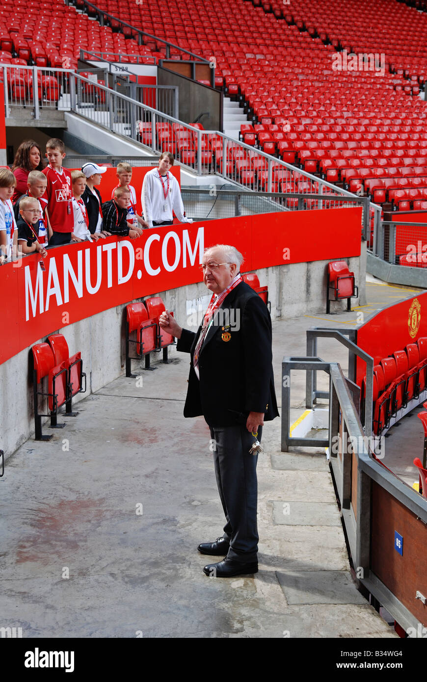 a stadium tour guide showing guests around old trafford, home of manchester united football club,manchester,uk - Stock Image