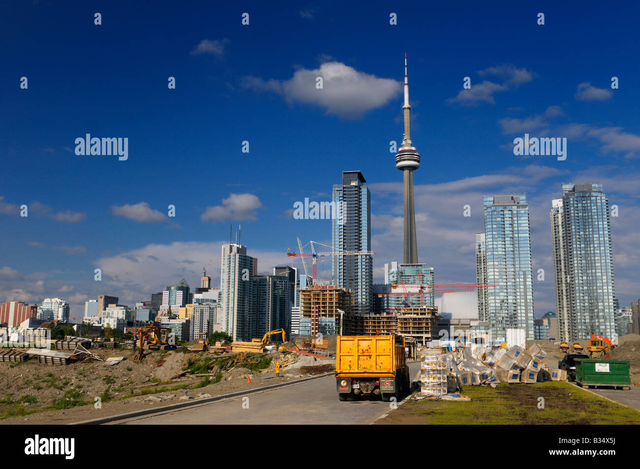 Construction dumpster truck and new condo development beside the city core of Toronto Canada with CN Tower - Stock Image
