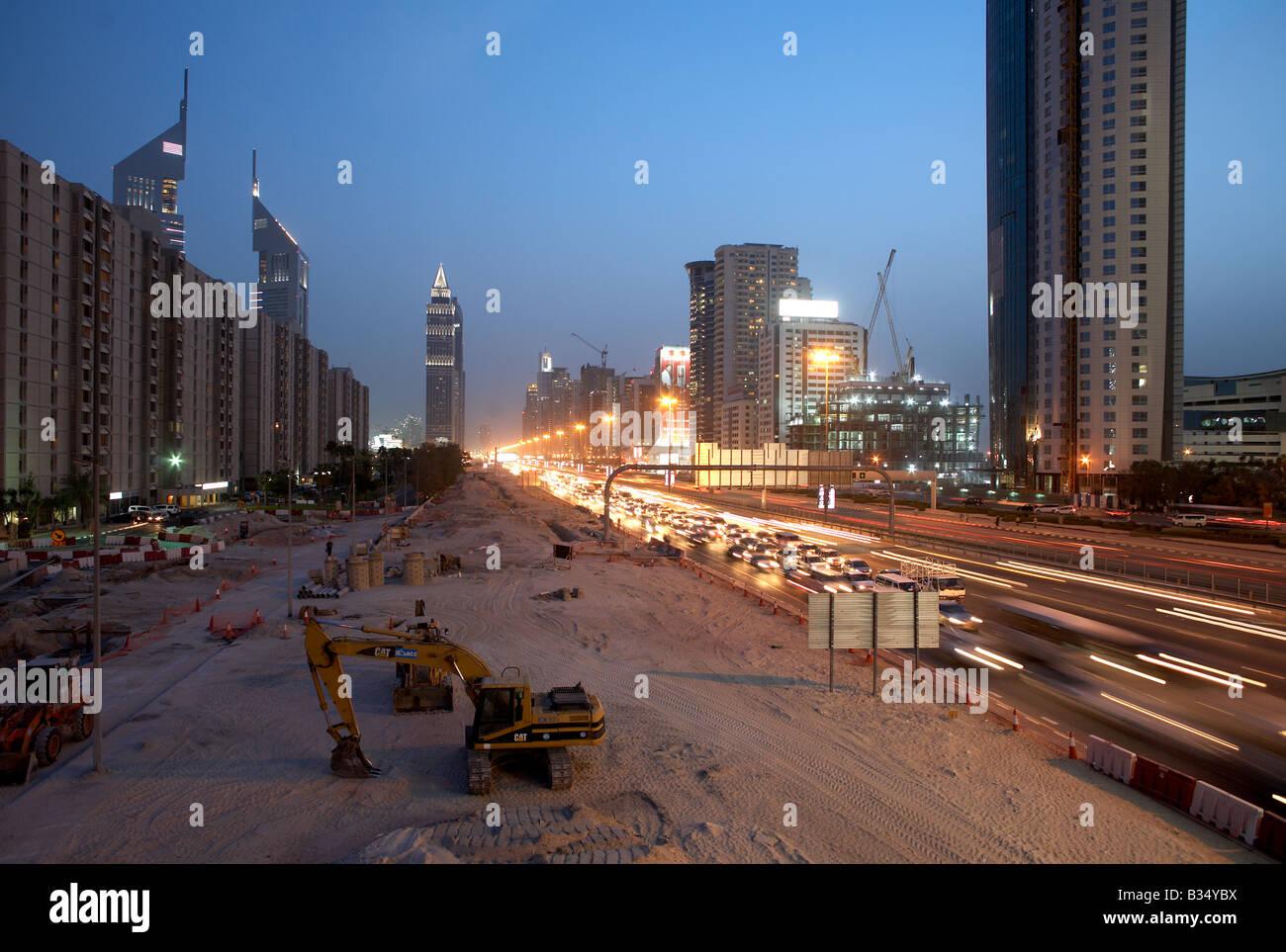 onstruction site with caterpillar on Sheikh Zayed Road at dusk Baustellenstreifen mit Bagger in der Dämmerung Stock Photo