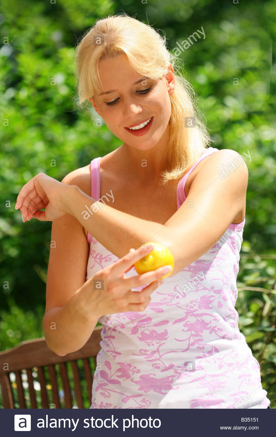 woman rubs the elbow with a lemon Stock Photo