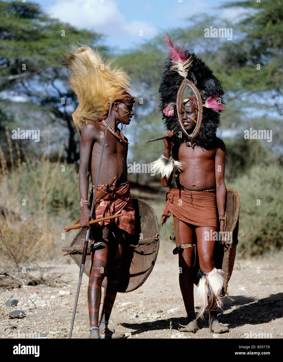 Kenya, kajiado, Ilpartimaro. Two Maasai warriors in full regalia. The headdress of the man on the left is made from - Stock Image