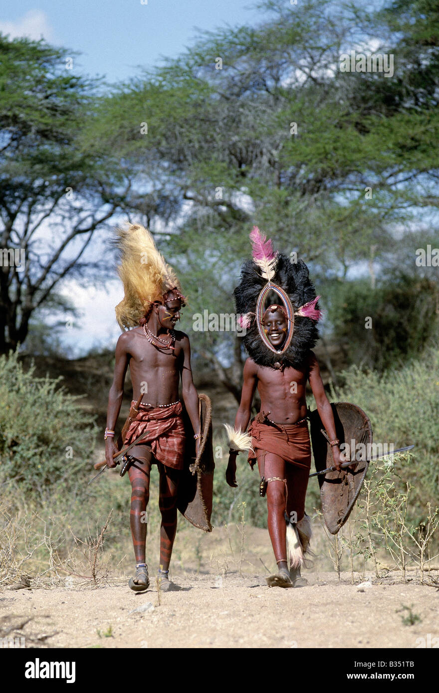 Kenya, Kajiado, lpartimaro. Two Maasai warriors in full regalia. The headress of the man on the left is made from - Stock Image