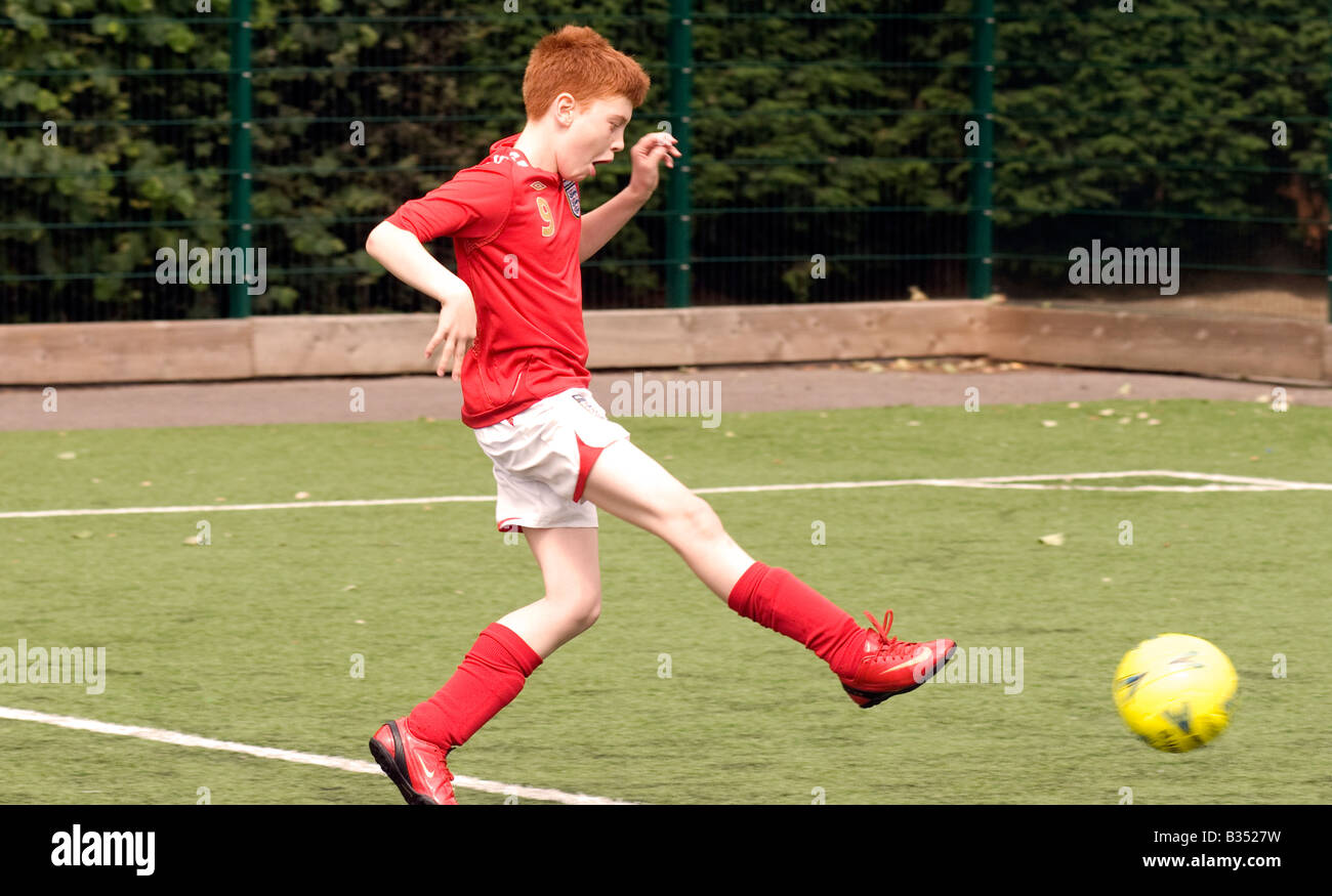 11 year old boy playing football, Maida Vale, London, UK