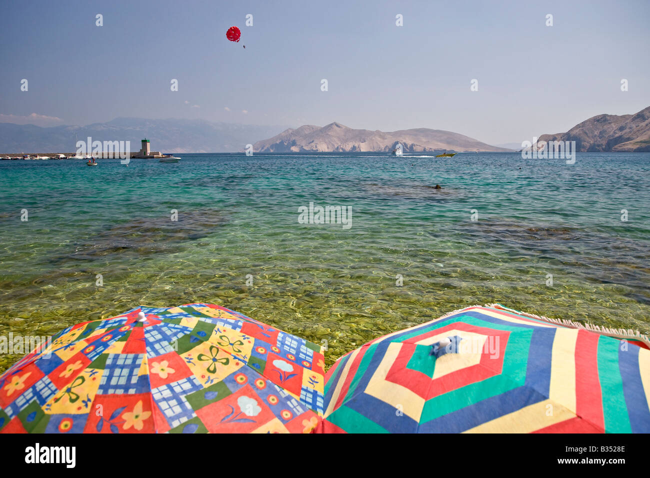 Two sunshades in front of the Baska bay at the isle of Krk in Croatia - Stock Image