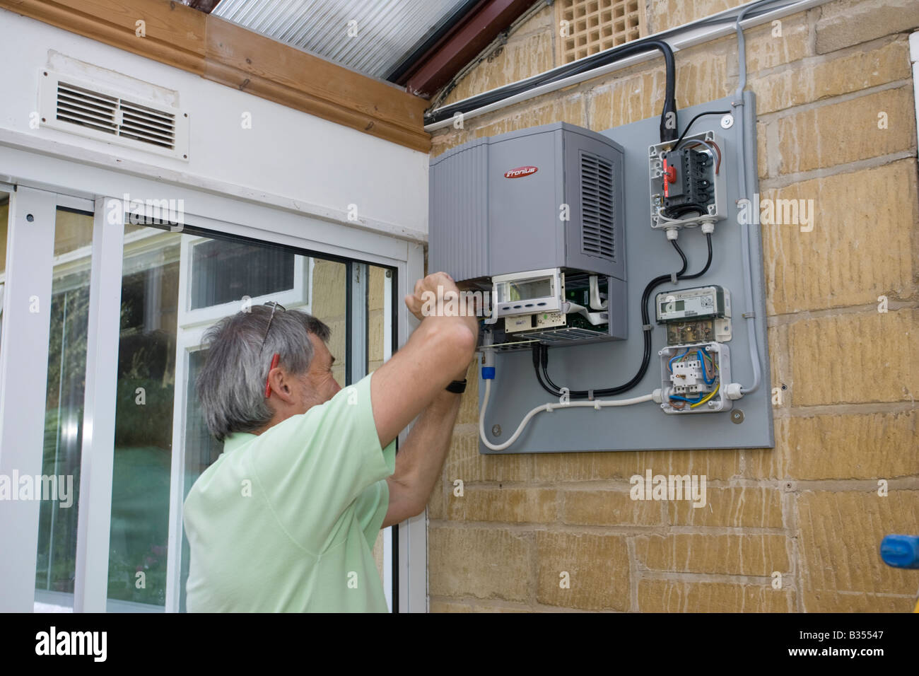 Solar inverter stock photos solar inverter stock images alamy electrician installing fronius inverter to control array of 12 solar pv panels cotswolds uk stock cheapraybanclubmaster Choice Image