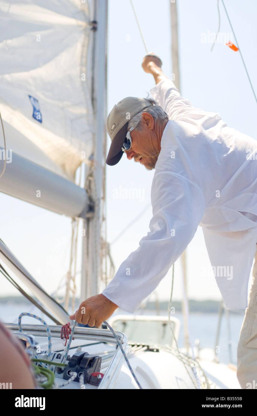 Skipper of Croatian Charter sailing yacht sets rigging - Stock Image