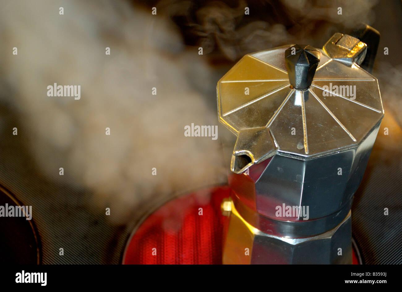 Stovetop moka espresso maker producing steam - Stock Image