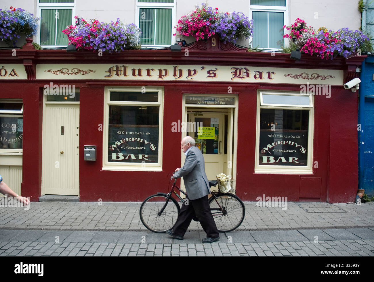 An eldrely man walks by Murphy's Bar in Galway city centre, Ireland - Stock Image