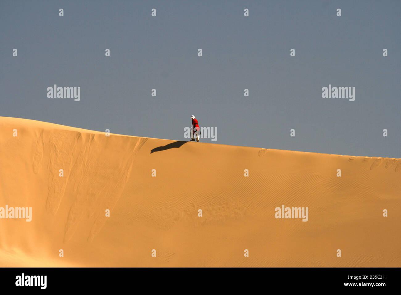 Solitary man walking on a sand dune In Akachaker Tassili Ahaggar Sahara desert Algeria - Stock Image