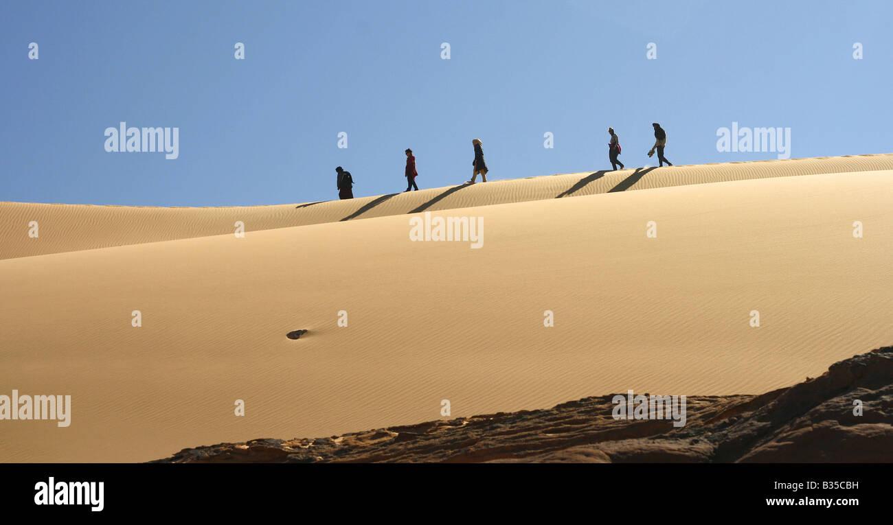 Persons walking on a sand dune In Akachaker Tassili Ahaggar Sahara desert Algeria - Stock Image