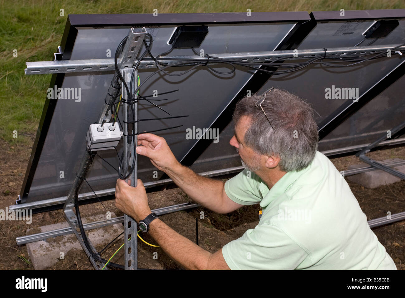 Amazing Electrician Installing Wiring On Array Of 12 Solar Hybrid Pv Panels Wiring Cloud Hisonuggs Outletorg