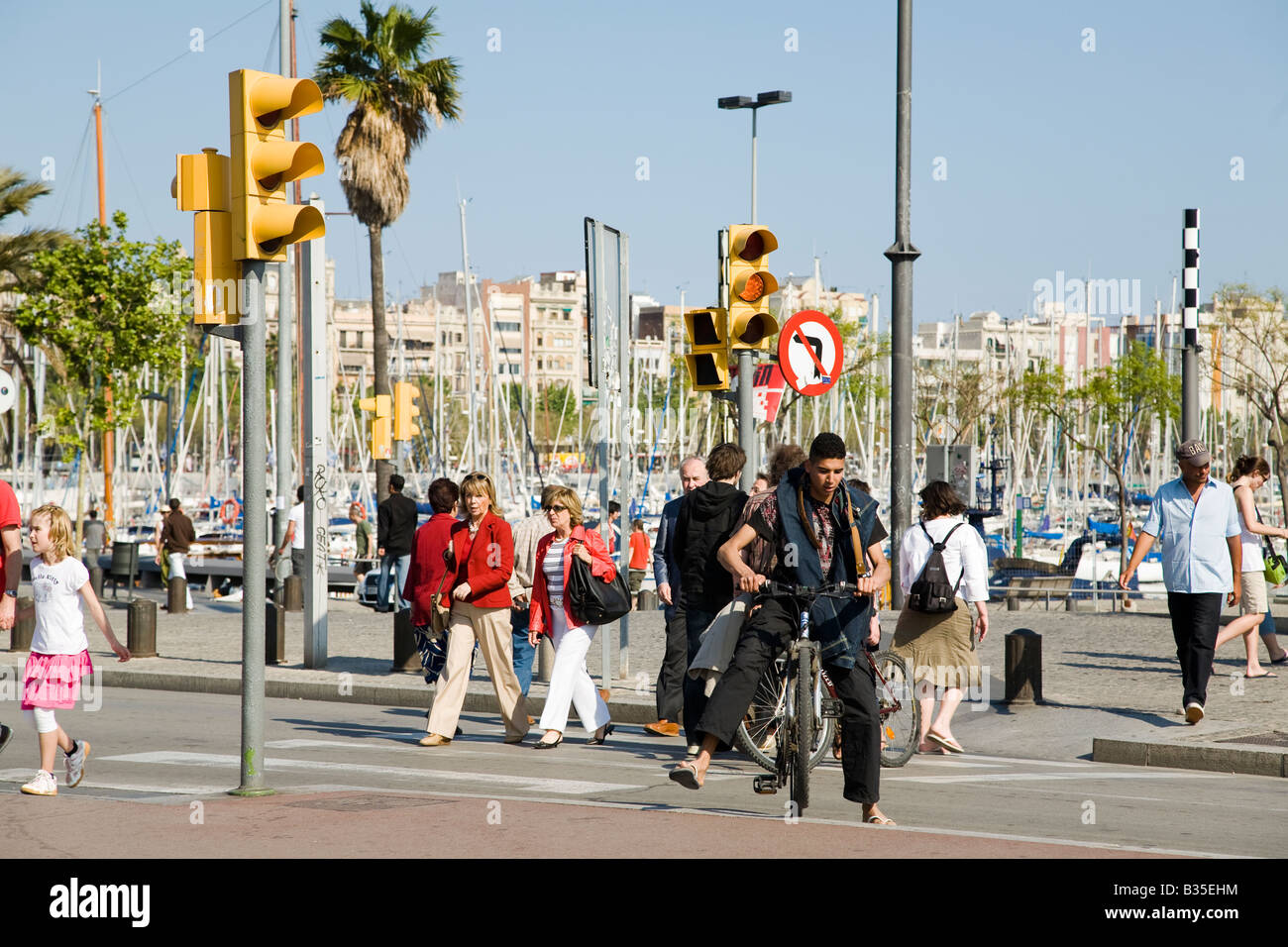 SPAIN Barcelona Pedestrians and male bicyclist in crosswalk near Marina Port Vell - Stock Image