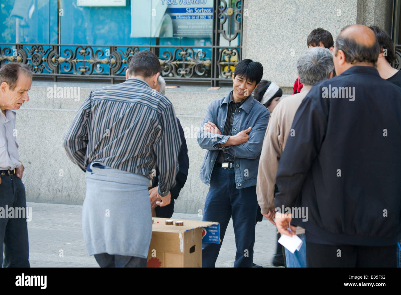 SPAIN Barcelona Man with skeptical expression watch shell game being played on sidewalk - Stock Image