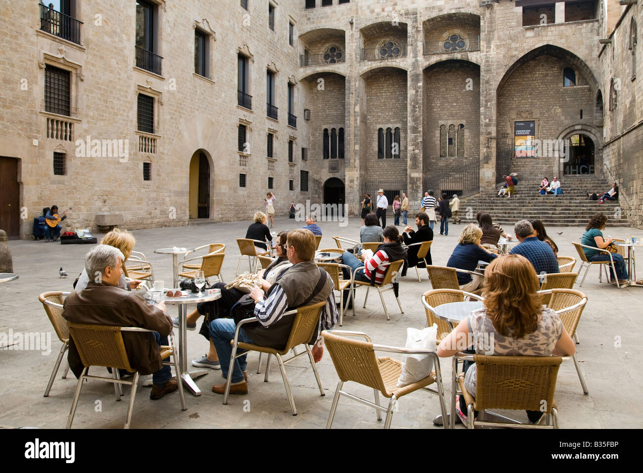 SPAIN Barcelona Couples sit at tables while female acoustic guitar playing in Placa del Rei plaza King s Square - Stock Image
