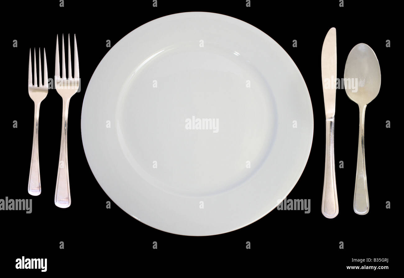 This is a place setting including one white dinner plate and silverware on a black background  sc 1 st  Alamy & This is a place setting including one white dinner plate and Stock ...