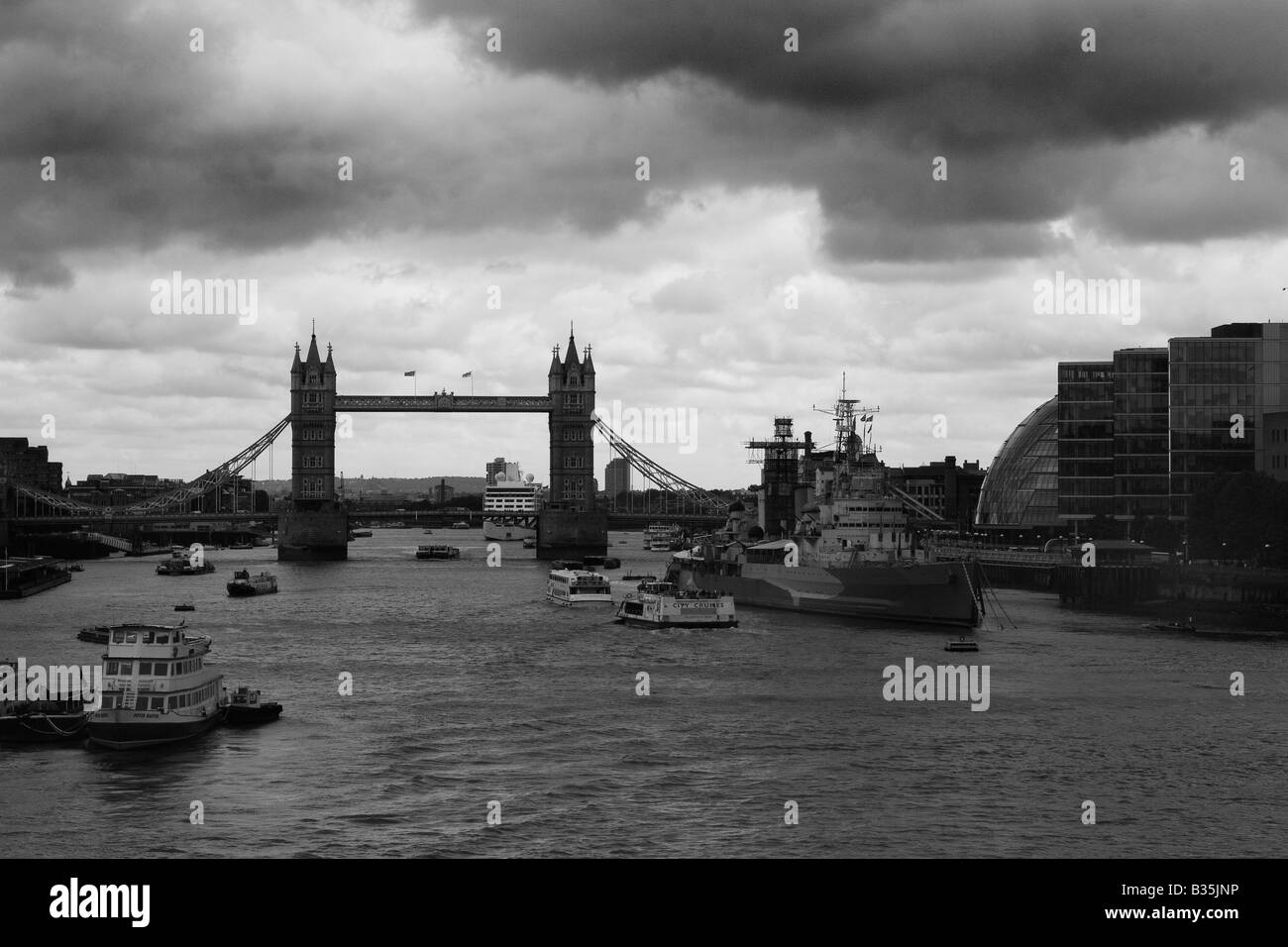 The Thames with Tower Bridge and HMS Belfast with dark storm clouds overhead - Stock Image